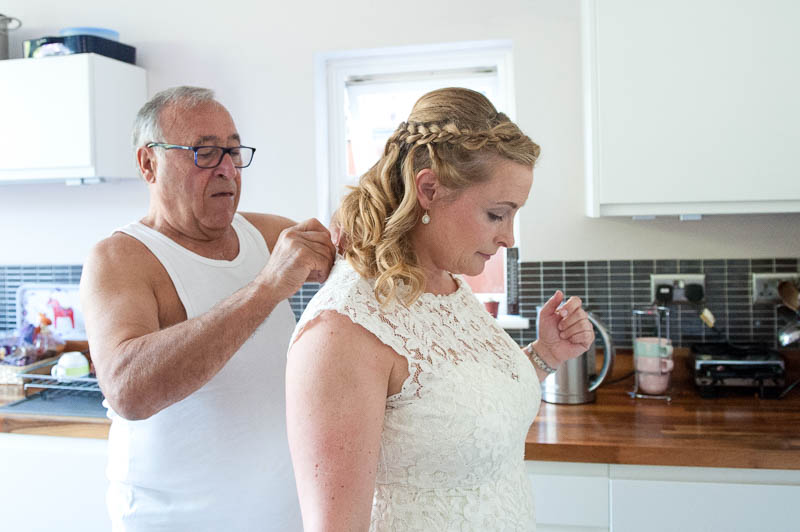 Documentary wedding photo of father helping bride into the wedding dress