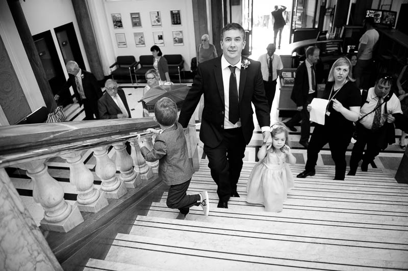 Groom walking up the stairs with his children at Islington Town Hall wedding