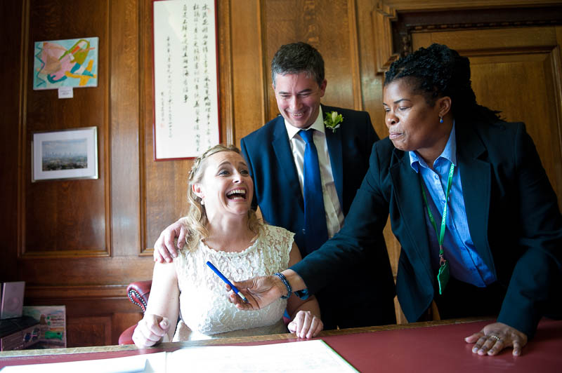 Bride and groom signing the register at Islington Town hall