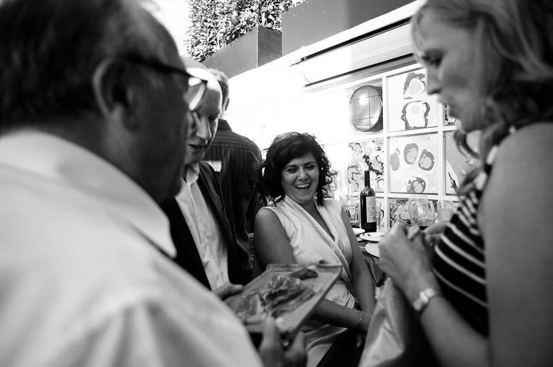 Black and white candid wedding photograph of guests mingling