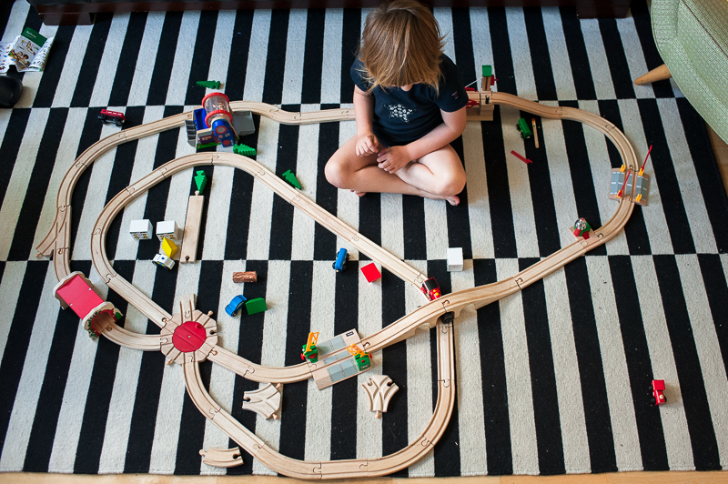 Boy playing with wooden train track