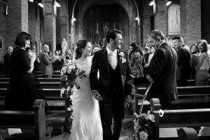 Bride and groom walking down the aisle at Our Lady of Lourdes and St Michaels church in Uxbridge
