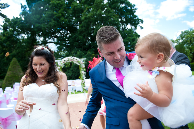 Bride, groom and daughter at outdoor wedding ceremony at Ridge Farm