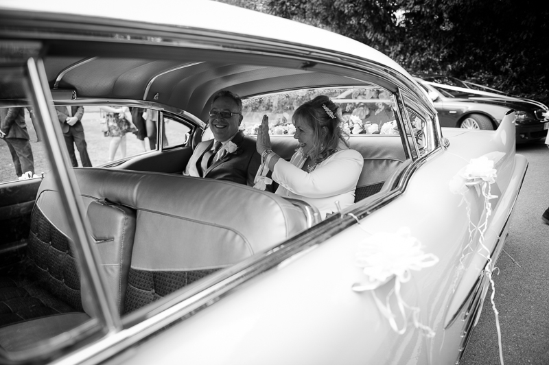 Bride and groom in pink cadillac
