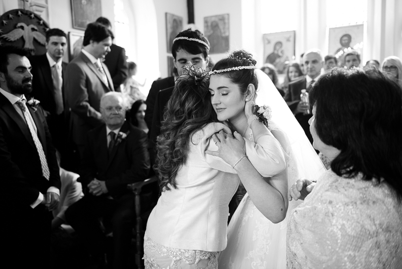Bride kisses mother at Greek wedding ceremony