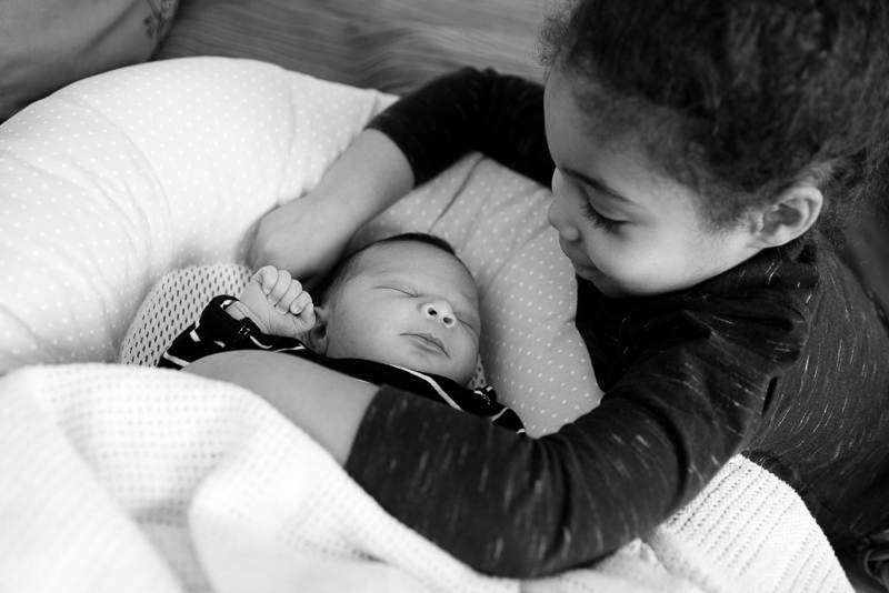 Black and white portrait of sister and newborn in Bounds Green