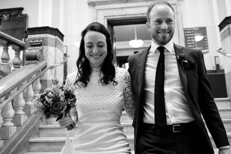 Bride and groom on marble staircase at Islington Town Hall