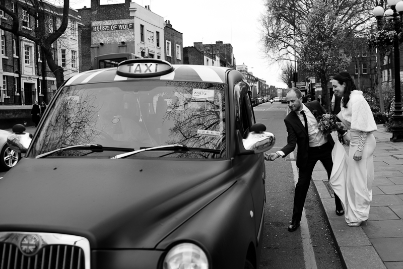 Bride and groom hail taxi outside Islington Town Hall
