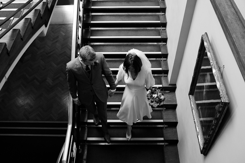 Bride and groom walking down the stairs at Stoke Newington Town Hall