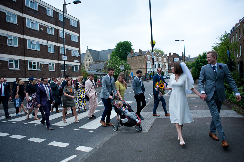 Bride and groom and wedding guests walk to wedding reception