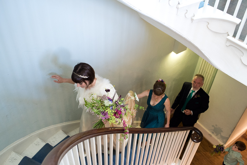 Bride walks up staircase at Clissold House