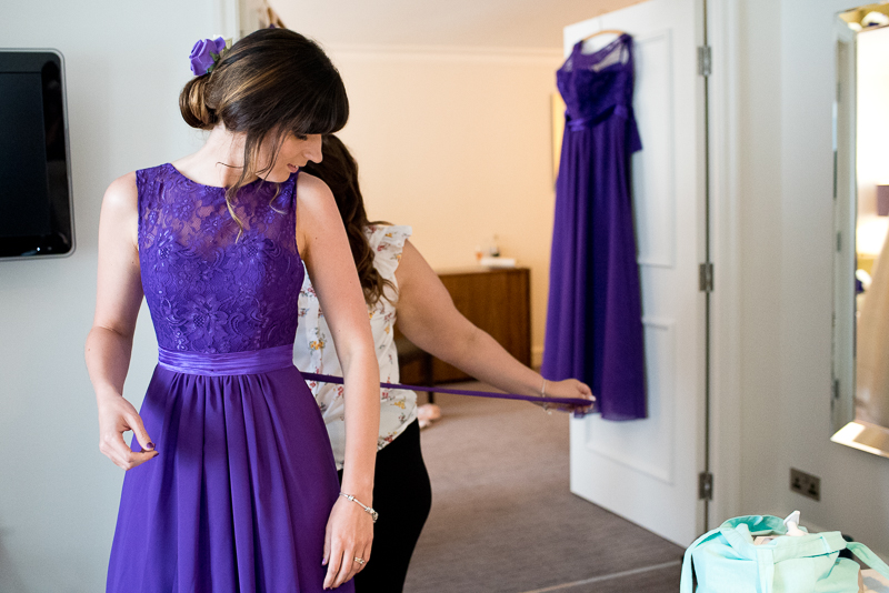 Bridesmaids putting on dress at Noke Hotel Wedding Reception