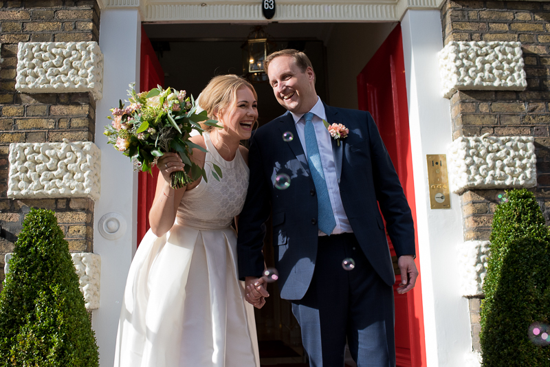Bride and groom outside red doors of Asia House
