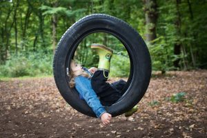 Girl on tyre swing in Coppetts Wood