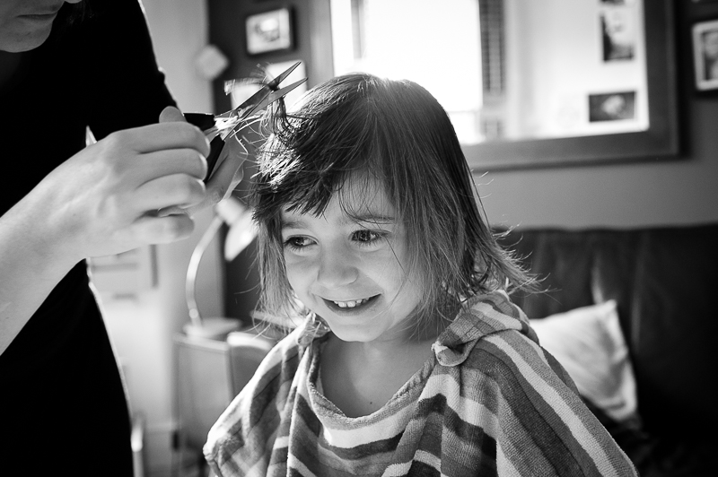 Boy with long hair getting haircut