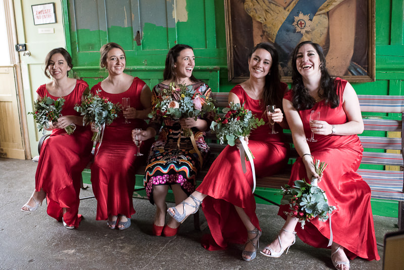 Bride with bridesmaids in red dresses at One Frienly Place