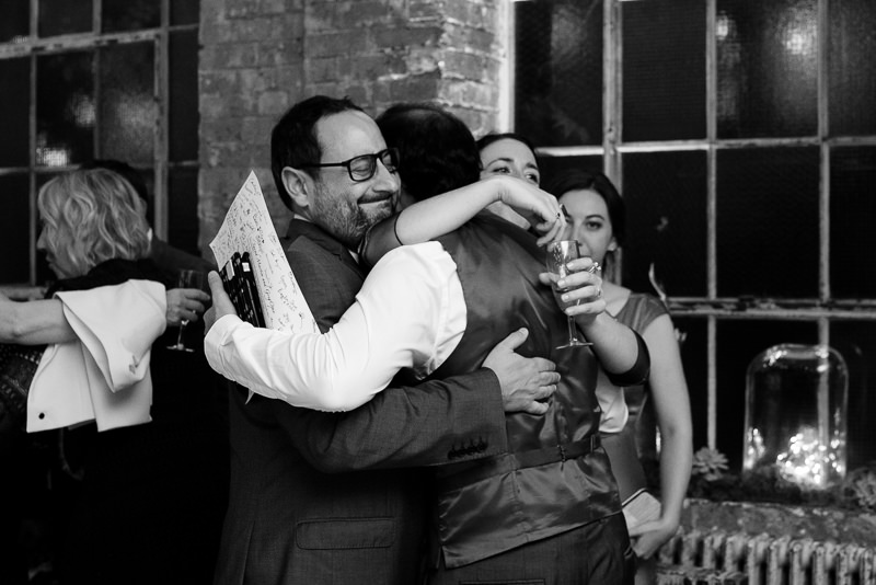 Bride and groom hug friends at One Friendly Place wedding