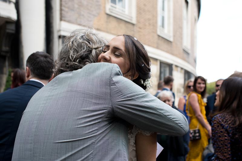 Bride hugs friend outside Stoke Newington Town Hall