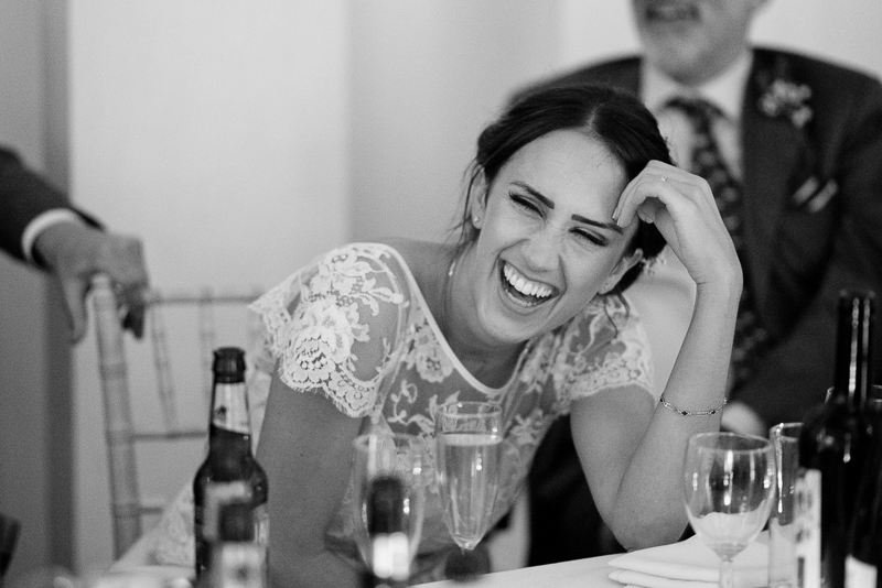 Bride laughing during speeches at West Reservoir Centre