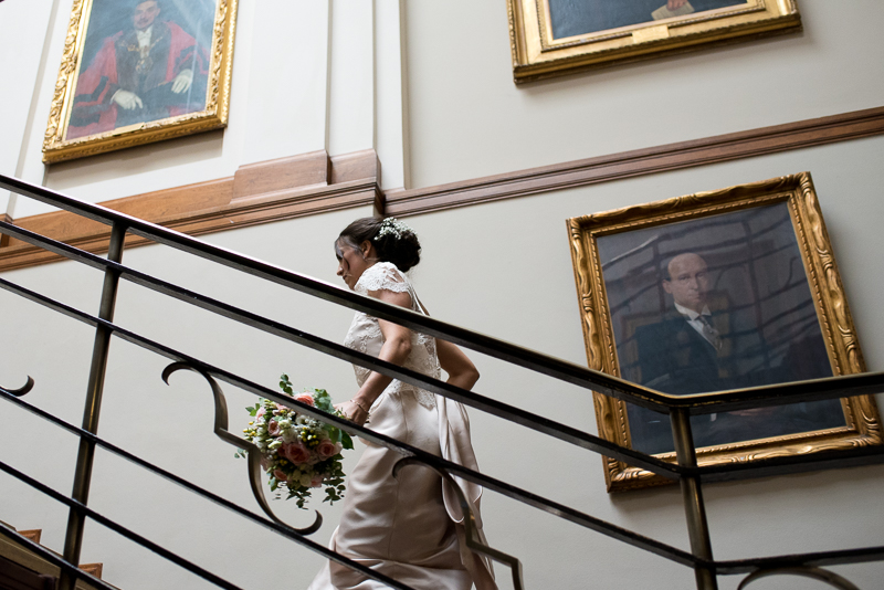 Bride makes her way up the stairs at Stoke Newington Town Hall wedding