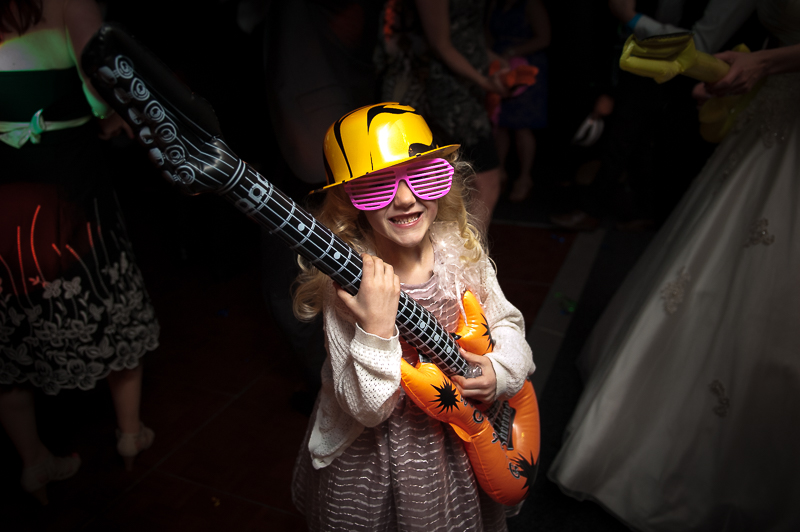 Child on dancefloor with blow up guitar at child-friendly wedding