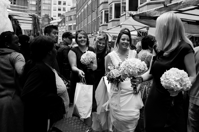 London bride walking through Petticoat Lane market on her way to Devonshire Terrace