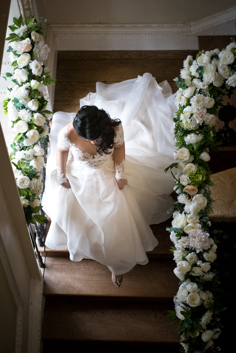 Bride walks down staircase at Boreham House wedding