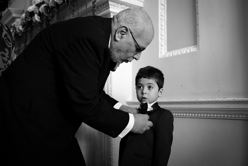 Grandpa puts button hole on ring bearer at Boreham House