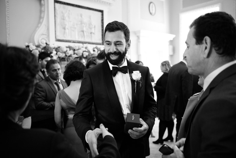Groom greets guests at Boreham House wedding