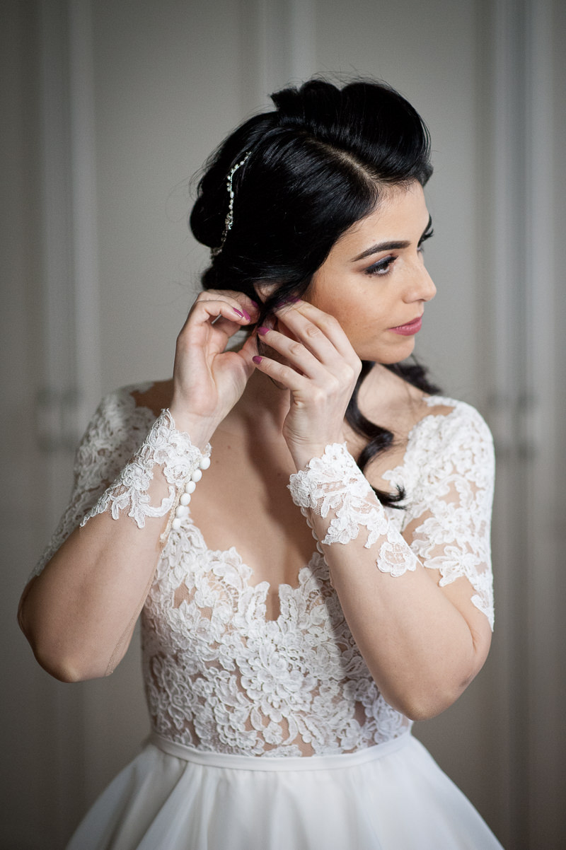 Bride putting on ear rings at Boreham House