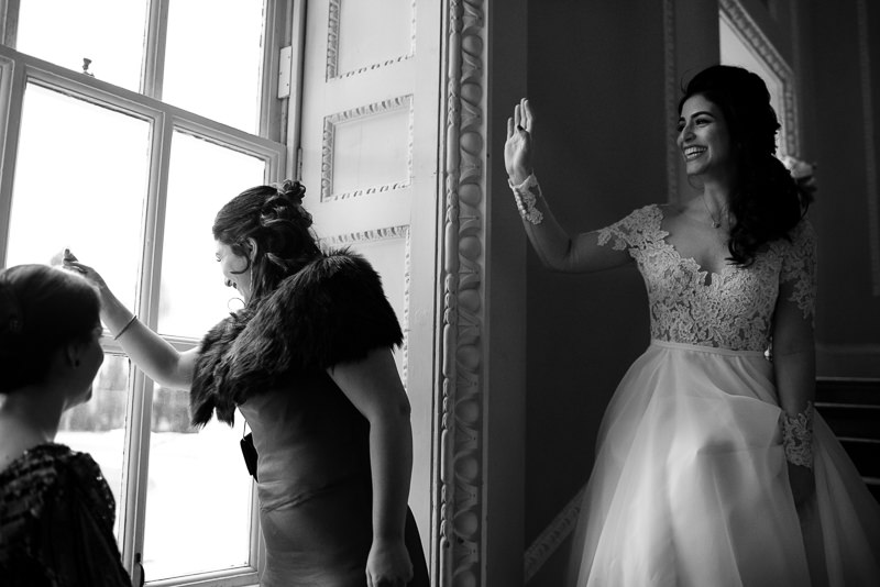 Bride with sisters waving at guests arriving for Boreham House wedding