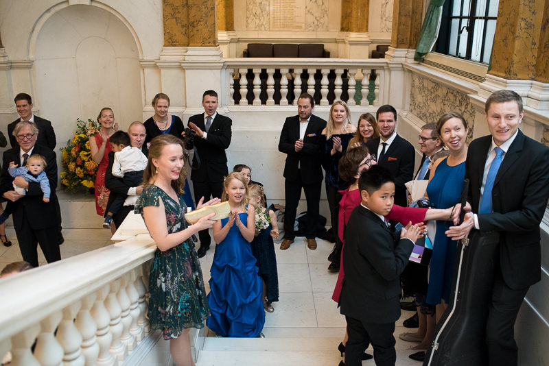Guests greet bride and groom on staircase at Camden Town Hall
