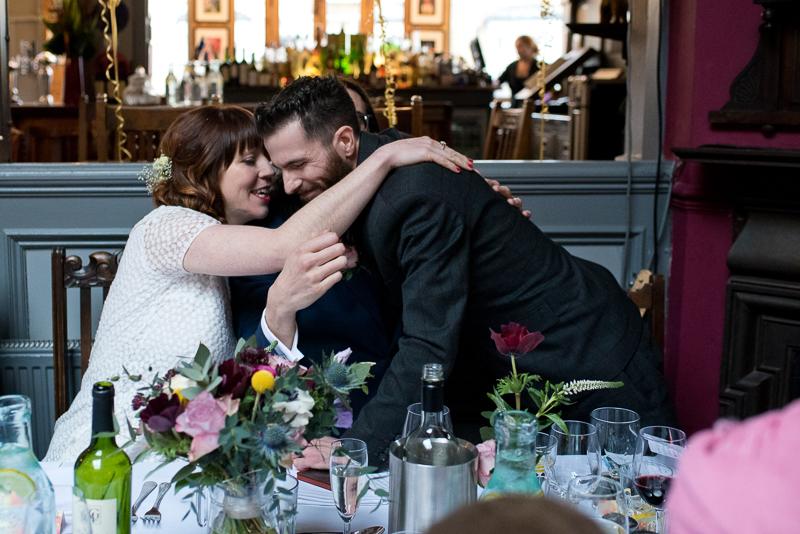 Couple hug best man after speeches at Stoke Newington wedding
