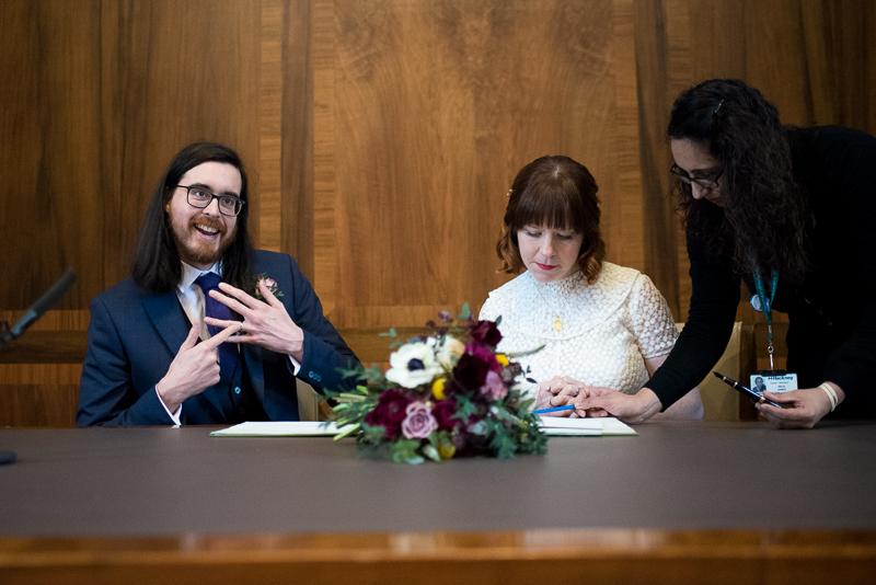 Bride and groom sign register at Stoke Newington wedding