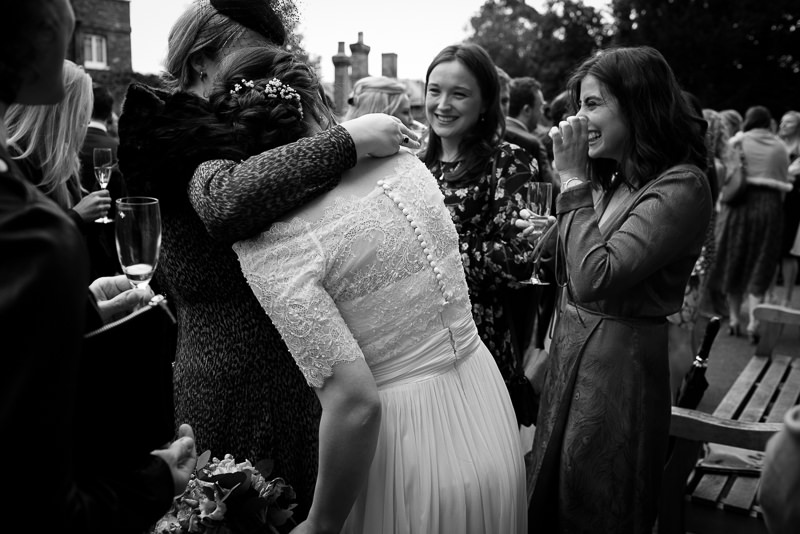 Bride greets best friends at Cambridge Cottage in Kew Gardens