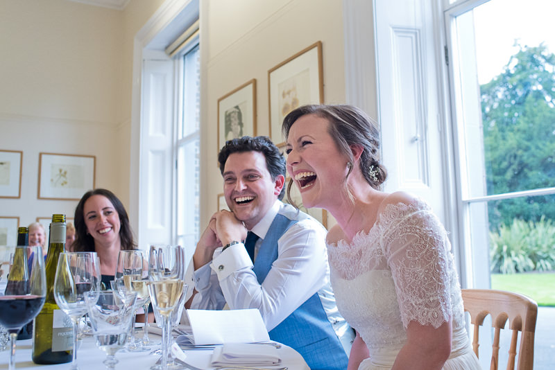Bride and groom laugh during speeches at Cambridge Cottage