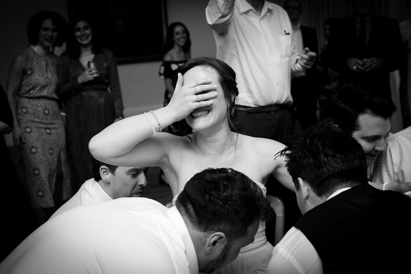 Bride gets lifted up on chair during Hora