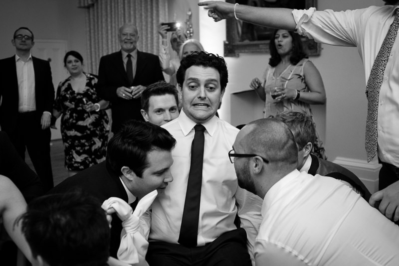 Groom gets lifted up on chair during Jewish wedding dance at Cambridge Cottage