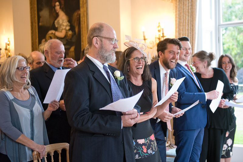 Guests laugh at wedding ceremony at Cambridge Cottage in Kew