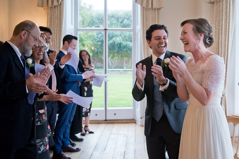 Natural photograph of bride and groom laughing during Cambridge Cottage wedding ceremony