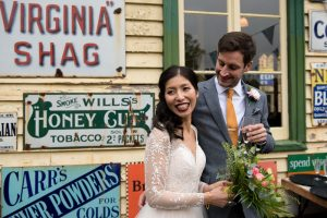 Bride and groom in front of colourful railway signs at Fawley Hill
