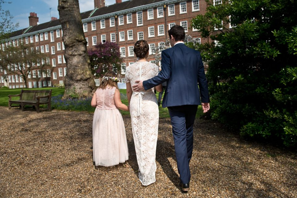 Bride, groom and flower girl walk to gardens at Gray's Inn wedding
