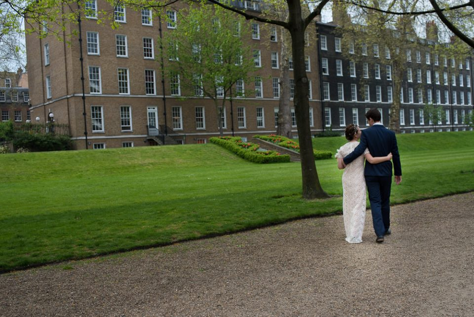 Bride and groom walk through the gardens at Gray's Inn