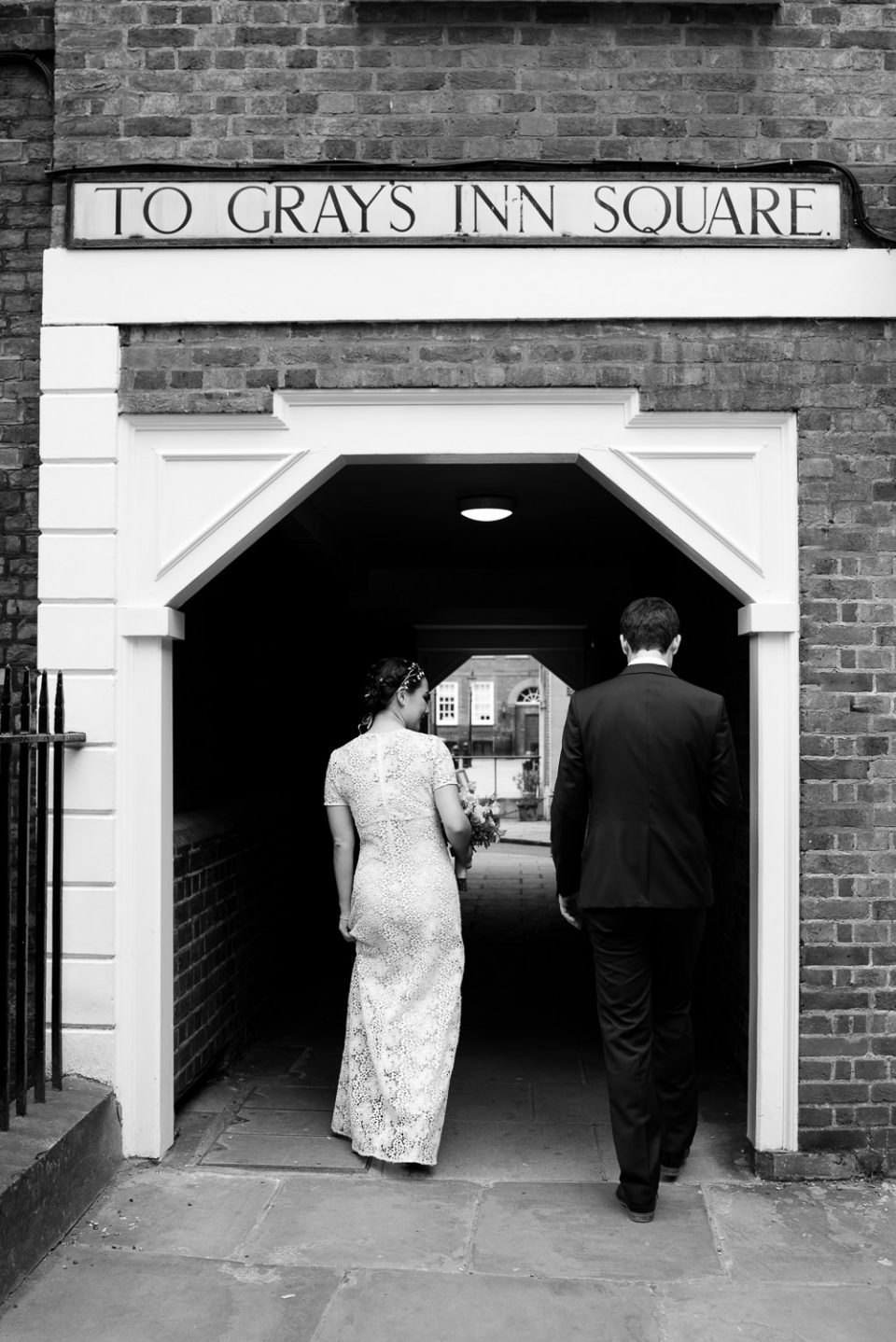 Candid Gray's Inn Wedding Photography of bride and groom going for a walk