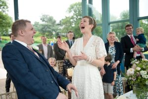 Bride and groom laugh at Horniman bandstand wedding