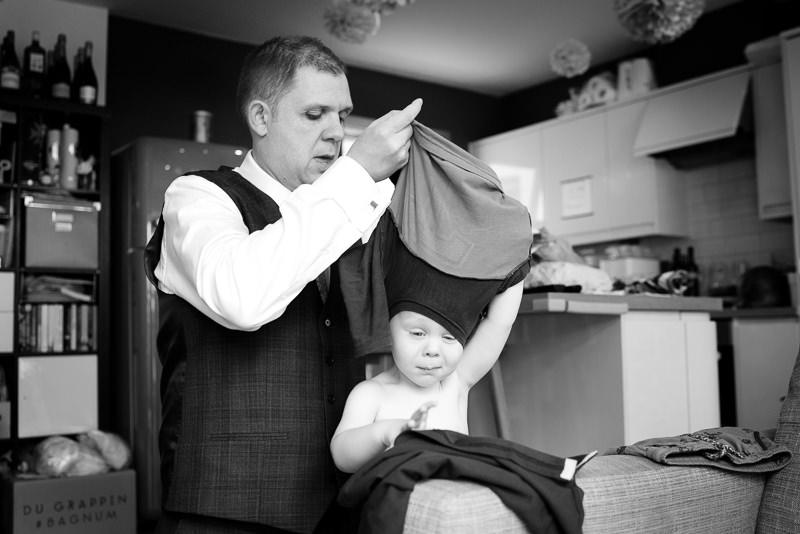 Groom helping son get dressed for Horniman bandstand wedding