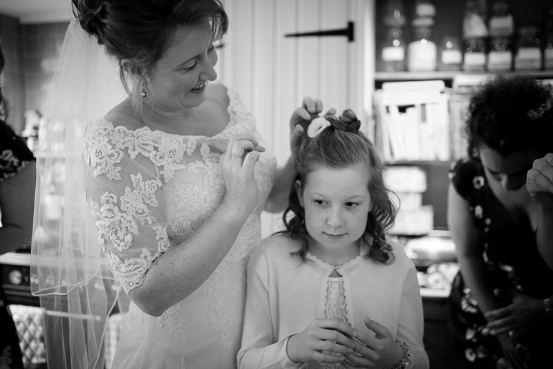 Bride puts flower in flowergirl's hair