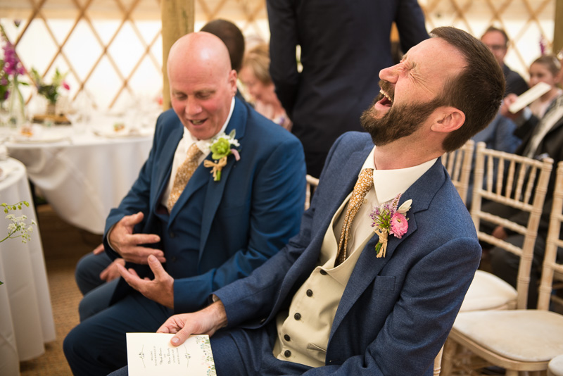 Groom laughing with best man at yurt wedding