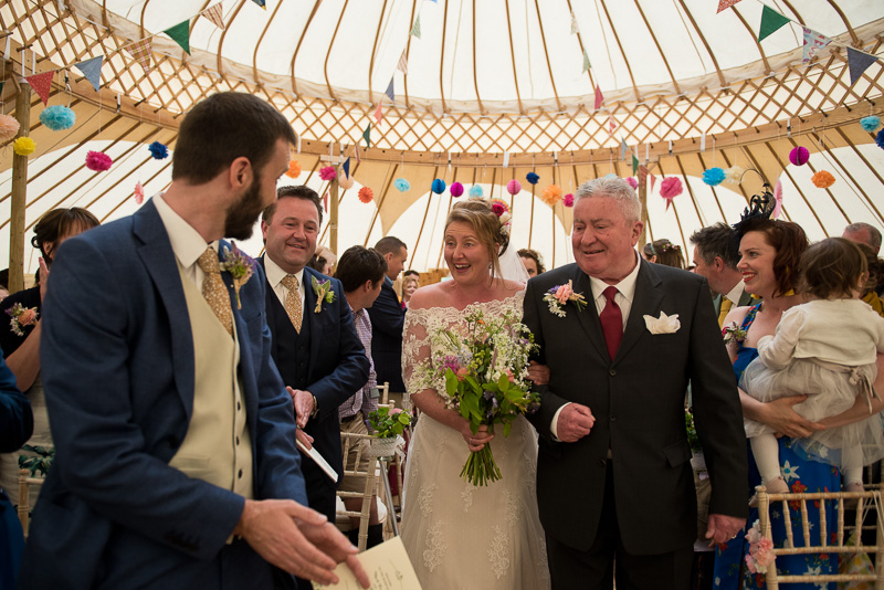 Bride walks up the aisle in yurt at North Hill Farm