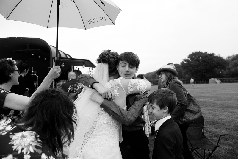 Documentary wedding photograph of bride hugging guests